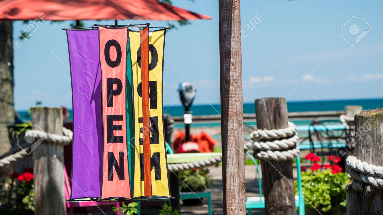The sign is open on the summer playground of a cozy cafe near the lake - 164730251