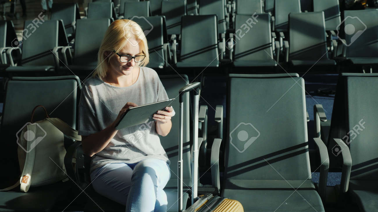 Caucasian woman is waiting for her flight. Sits in the airport terminal, uses a tablet - 167296584