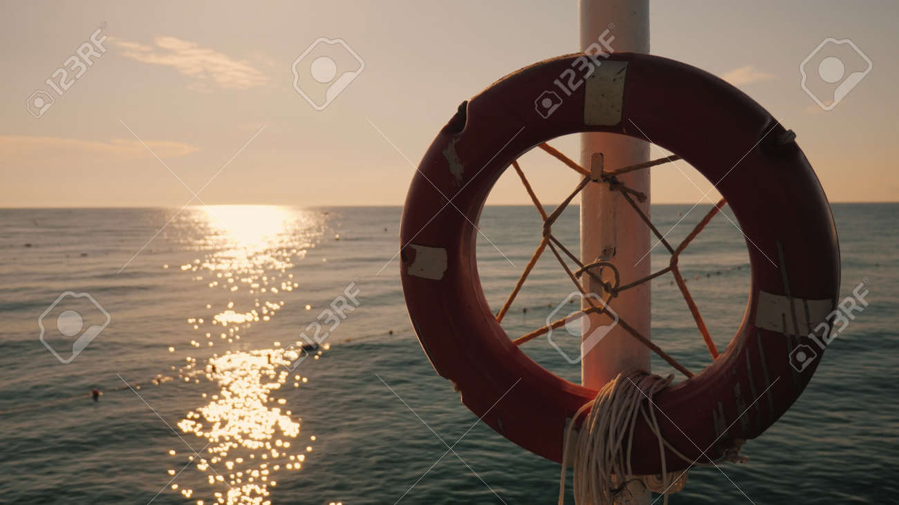 Lifebuoy hanging on the background of the sea at sunrise. Morning at the sea - 167148784