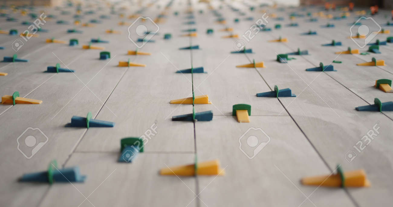 Ceramic tiles, just laid on the floor, in the form of boards, fixed with a leveling system - 168647975