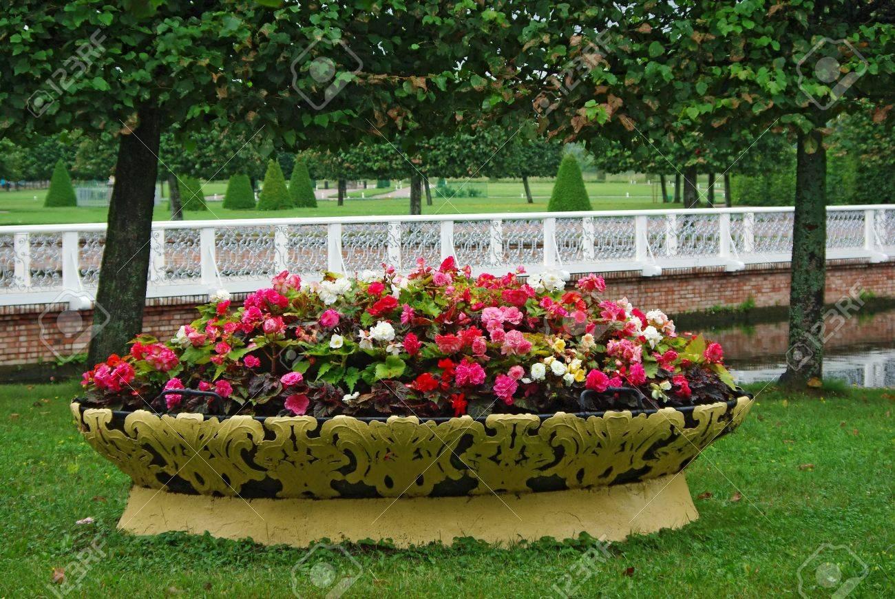 jardinera llena de flores de todos colores en frente de la valla blanca foto de archivo