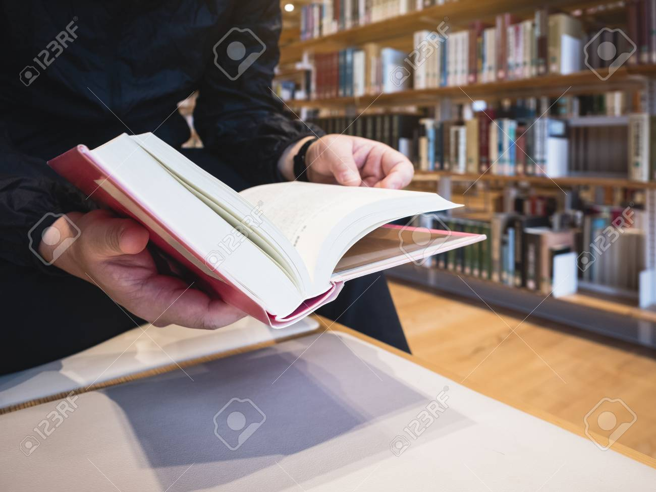 People Reading Book Open Page Bookshelf In Library Education Concept Stock Photo