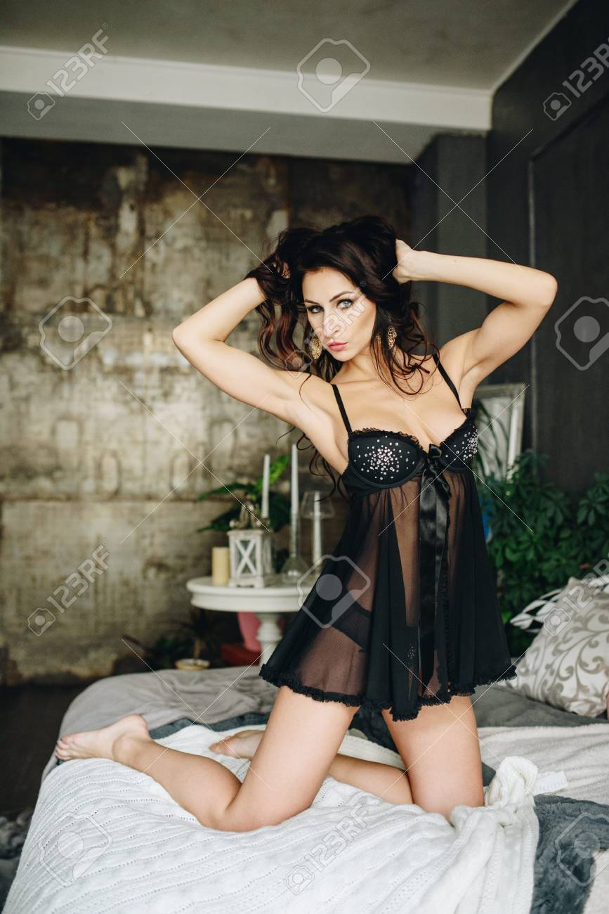 26244ccd9 Beautiful woman in lingerie showing long legs sexy pose sitting at bed over  her bedroom with