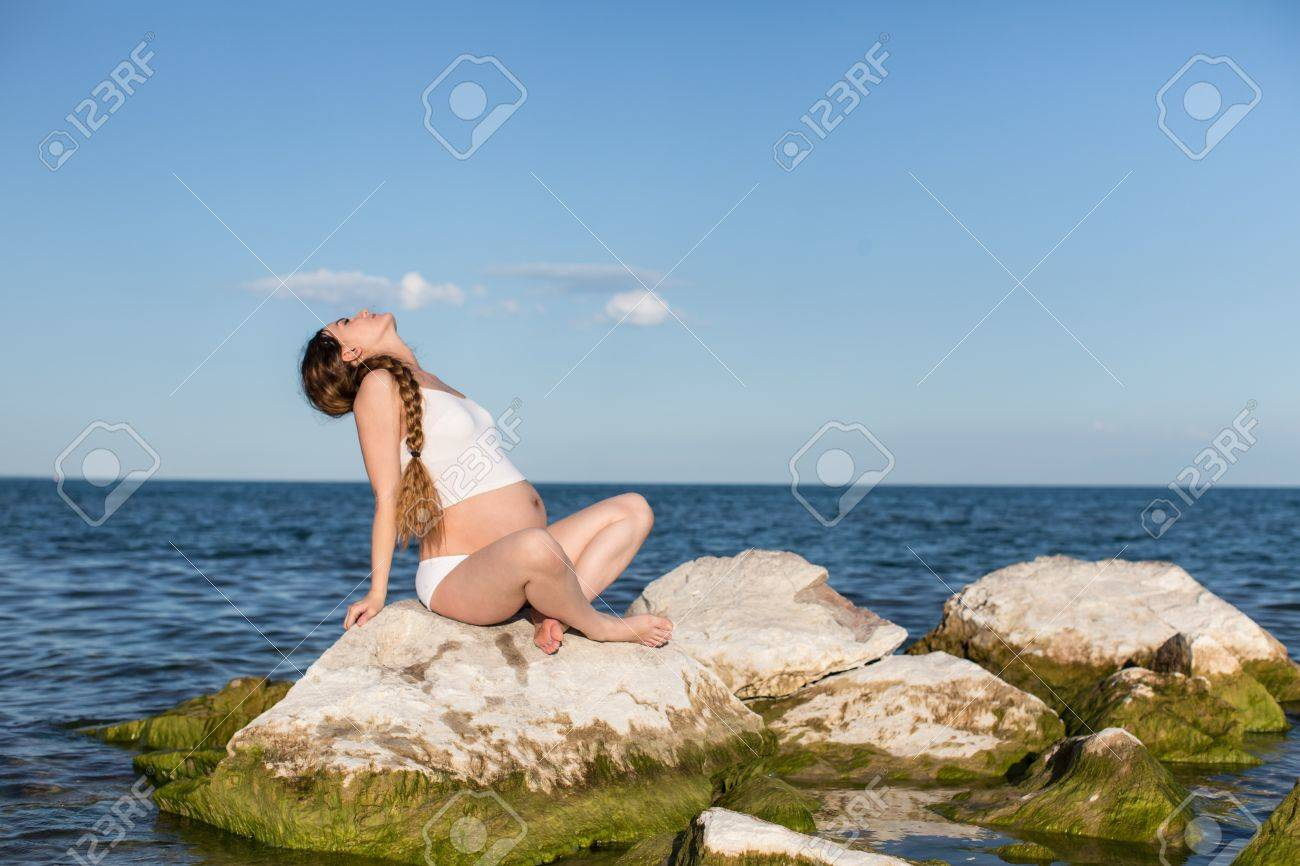 1274c5193a Pregnant woman in sports bra doing exercise in relaxation on yoga pose on  ocean Stock Photo