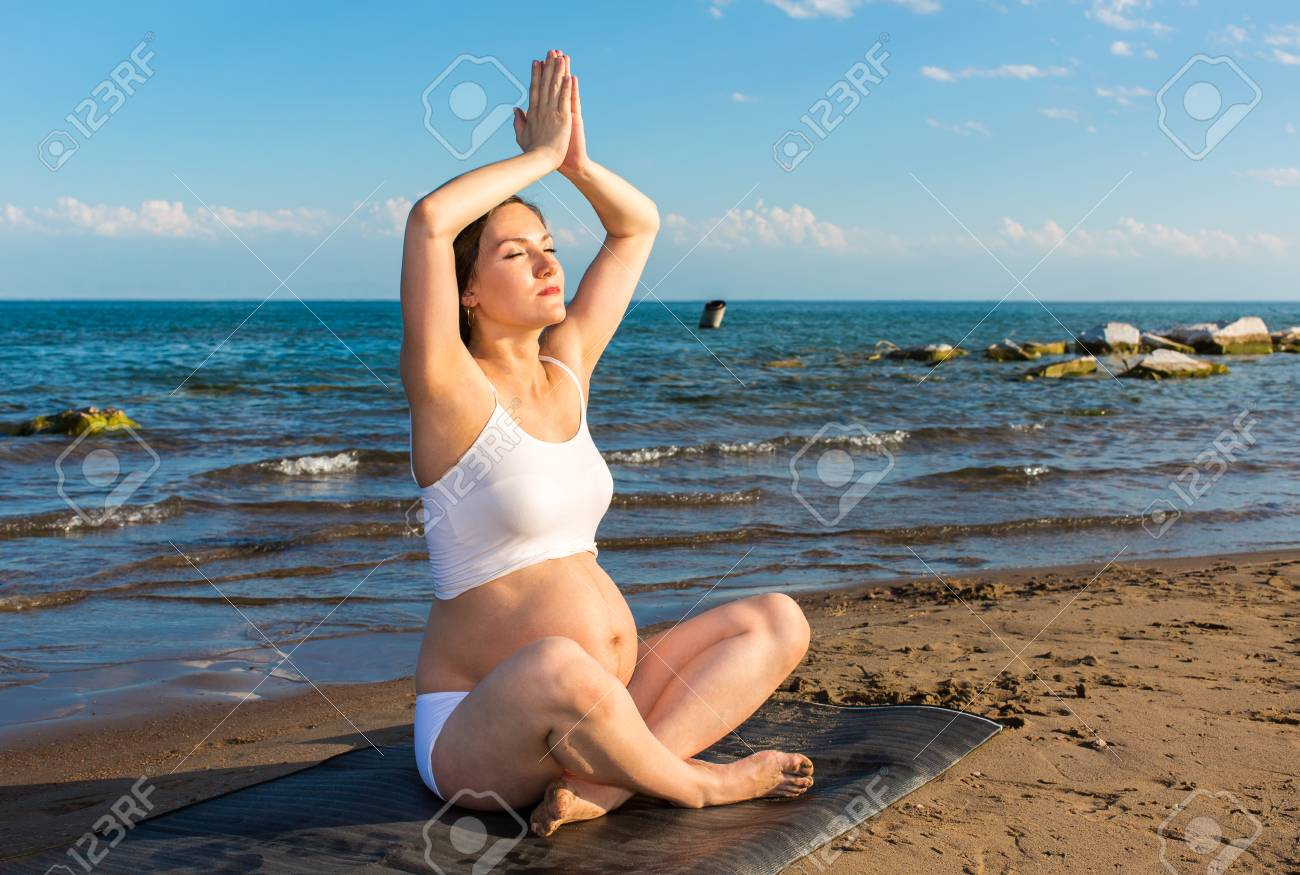 28422d8e24 Pregnant woman in sports bra doing exercise in relaxation on yoga pose on  sea Stock Photo
