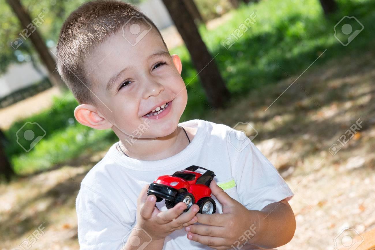 かわいい子男の子は夏に自然の公園でおもちゃの車を再生します。赤ちゃん