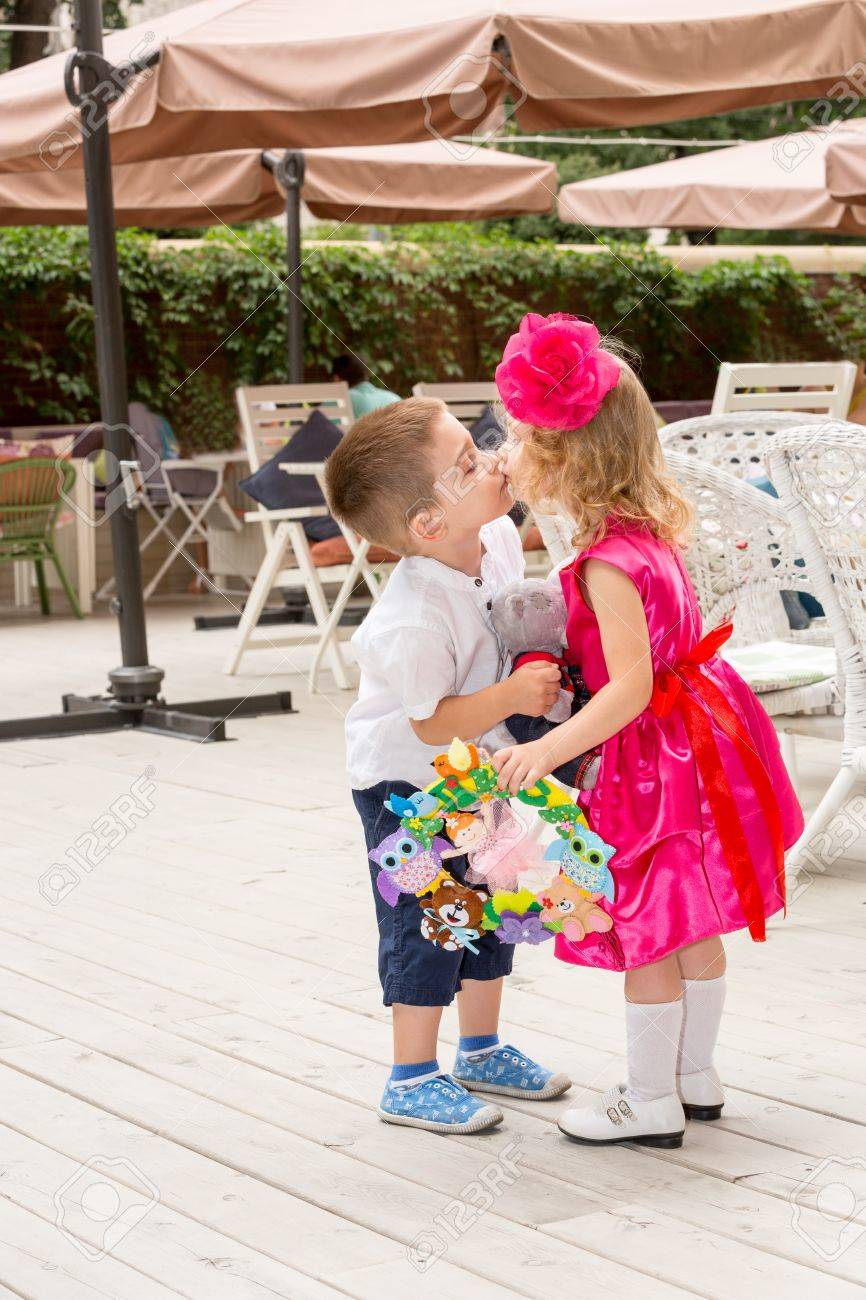 The Boy Kid Gives Flowers And Kissing Girl Child On Birthday