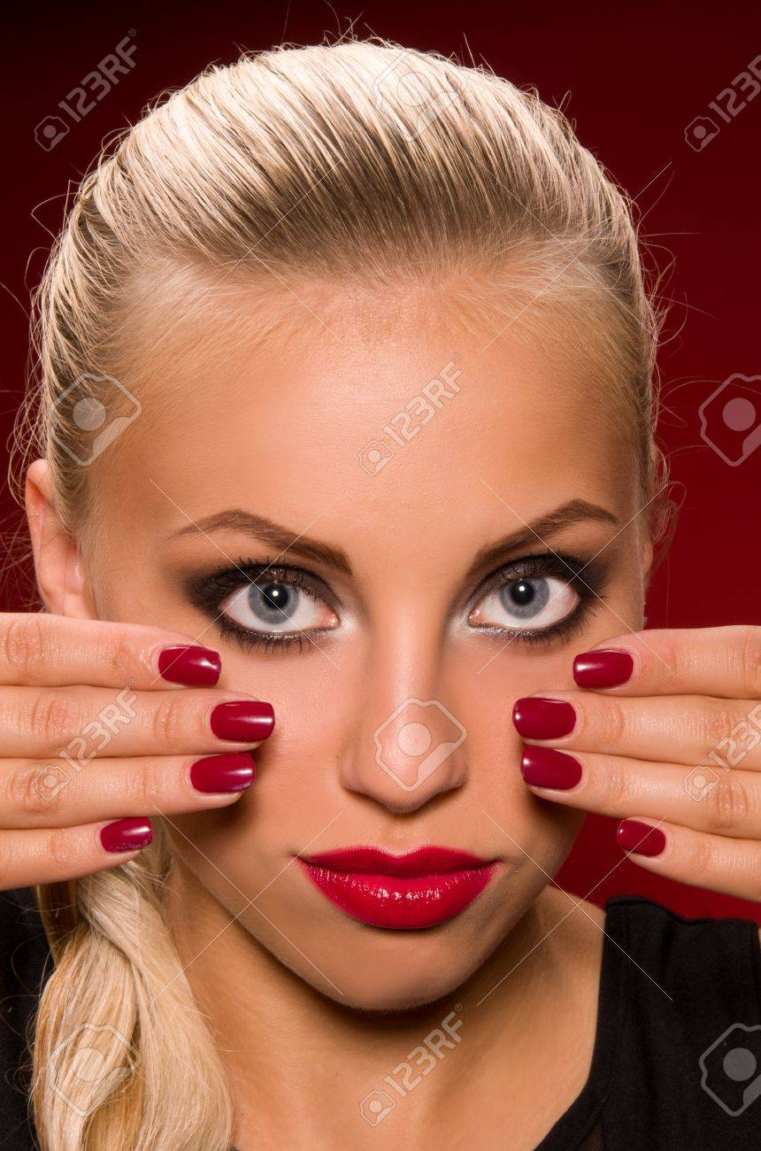 sexy girl with aggressive makeup on a dark red background Stock Photo - 16512344