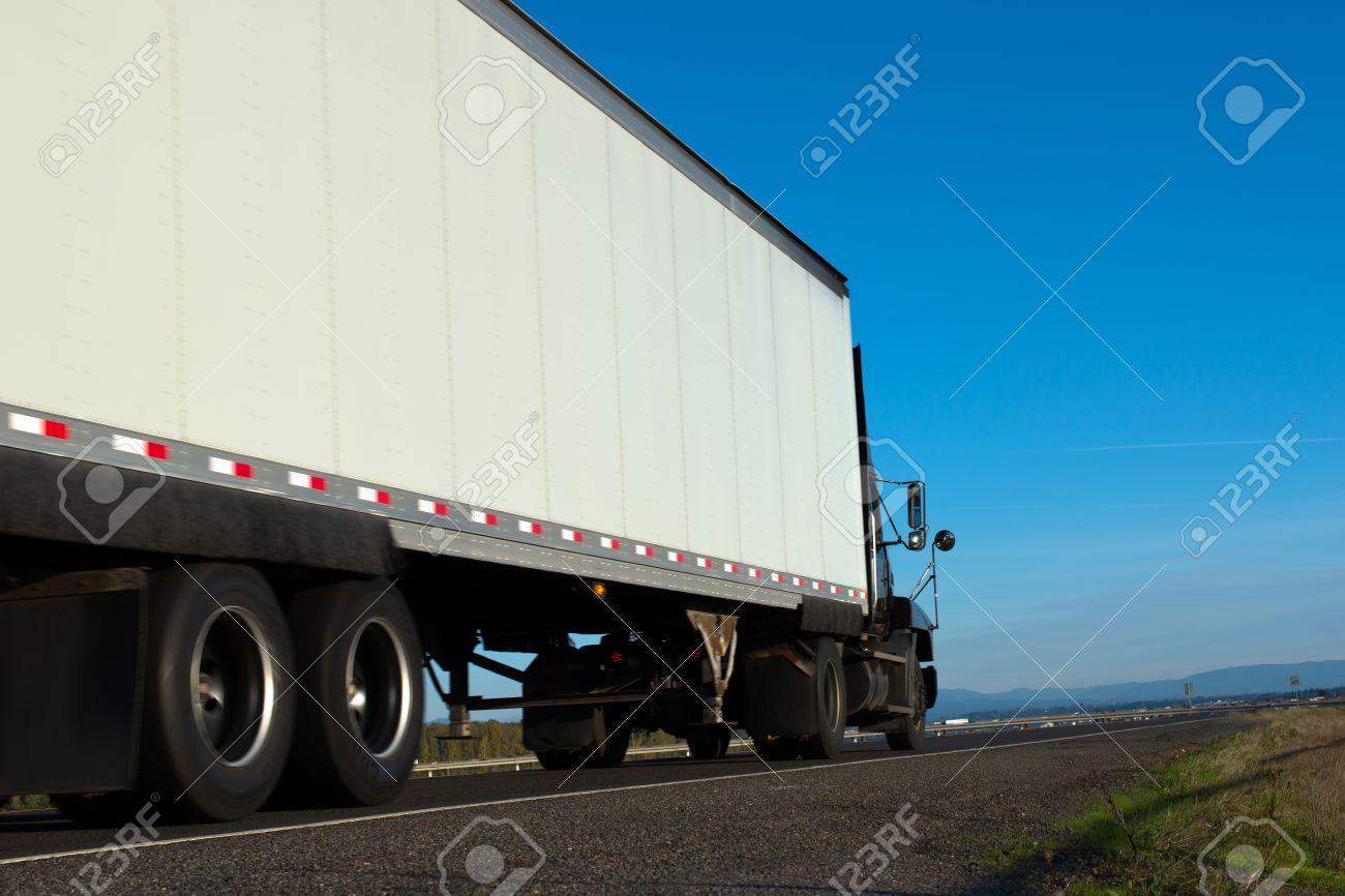 big dark semi truck and white trailer on the road with bridge