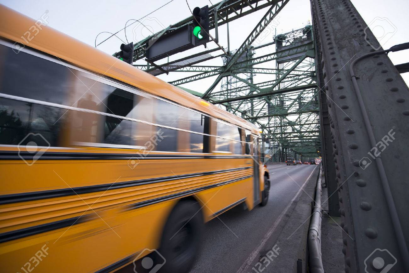 long blurred in motion yellow school bus moves on the metal truss