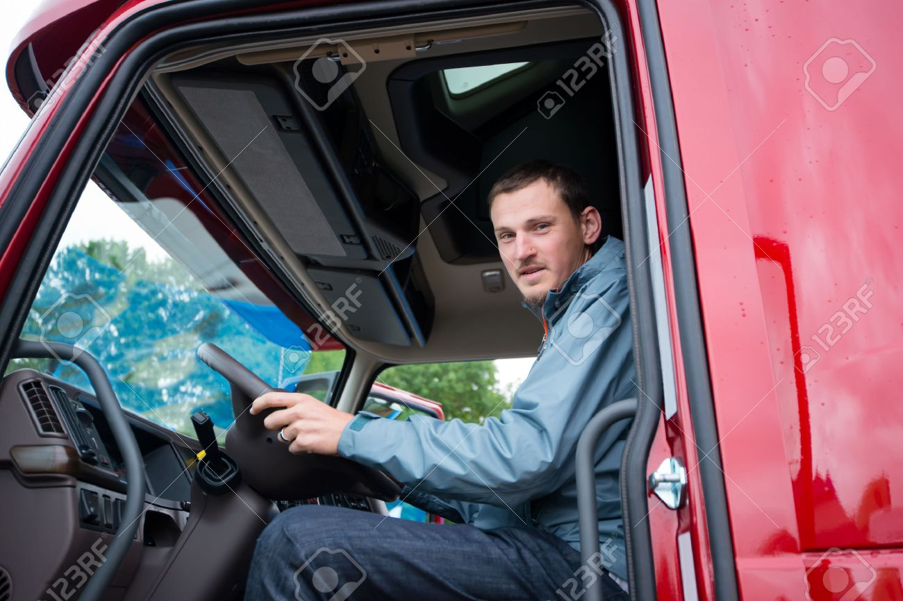 This image has an empty alt attribute; its file name is 47319293-happy-truck-driver-sitting-in-the-cab-of-red-truck-behind-the-wheel-and-looking-through-the-open-doo.jpg