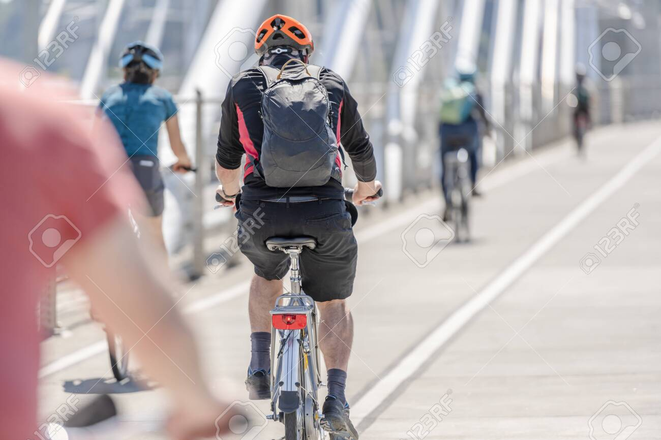 The people on the bicycles pedals a bike preferring an active healthy lifestyle using cycling and alternative environmentally friendly mode of transport in order to preserve nature environment - 129029798