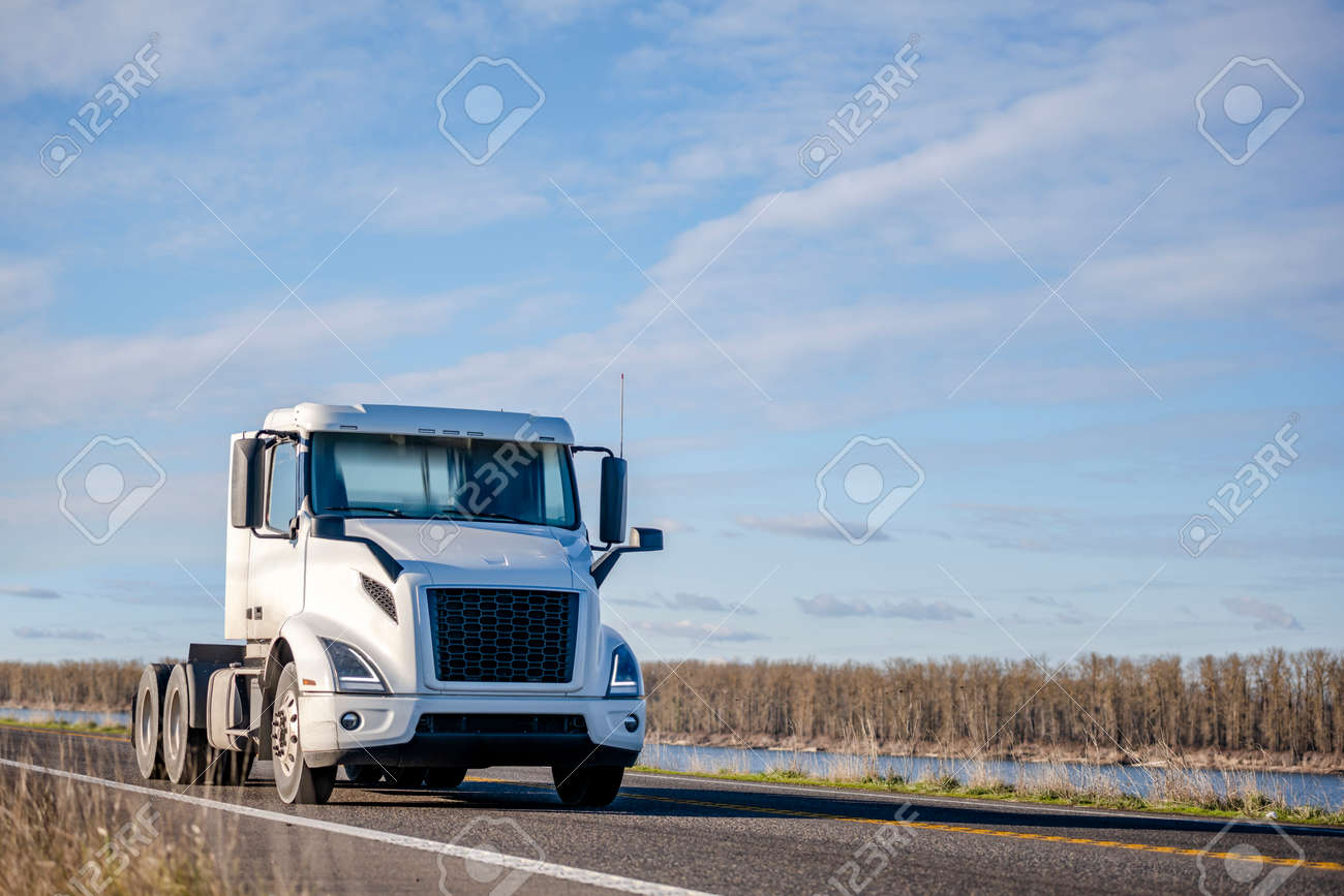 Powerful Big rig white day cab semi truck tractor without semi trailer running on the narrow highway road along the river to warehouse for pick up the next loaded trailer for delivery - 167018119