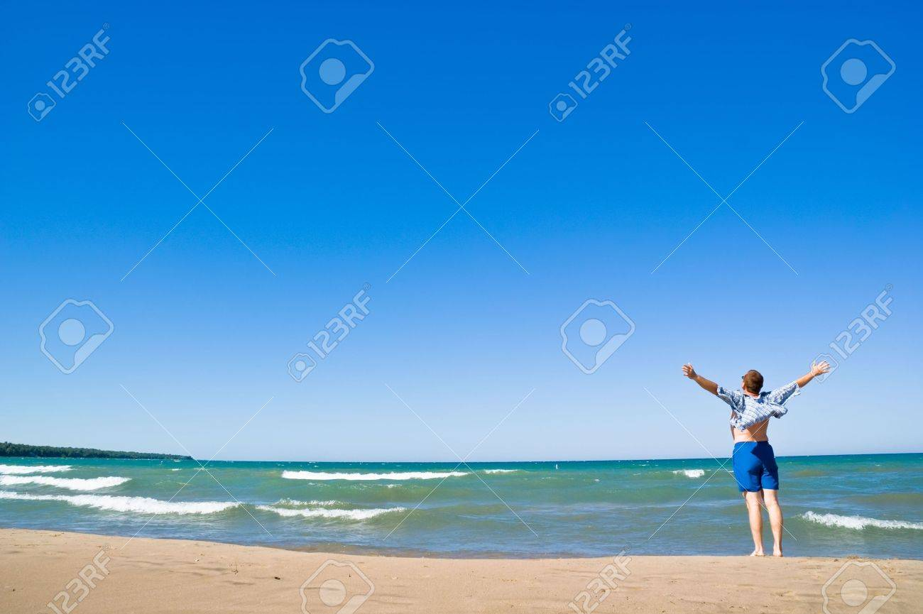 Man with arms outstretched standing on the lakeshore and looking up. Sand beach and blue water. Summer, vacation. - 5420526