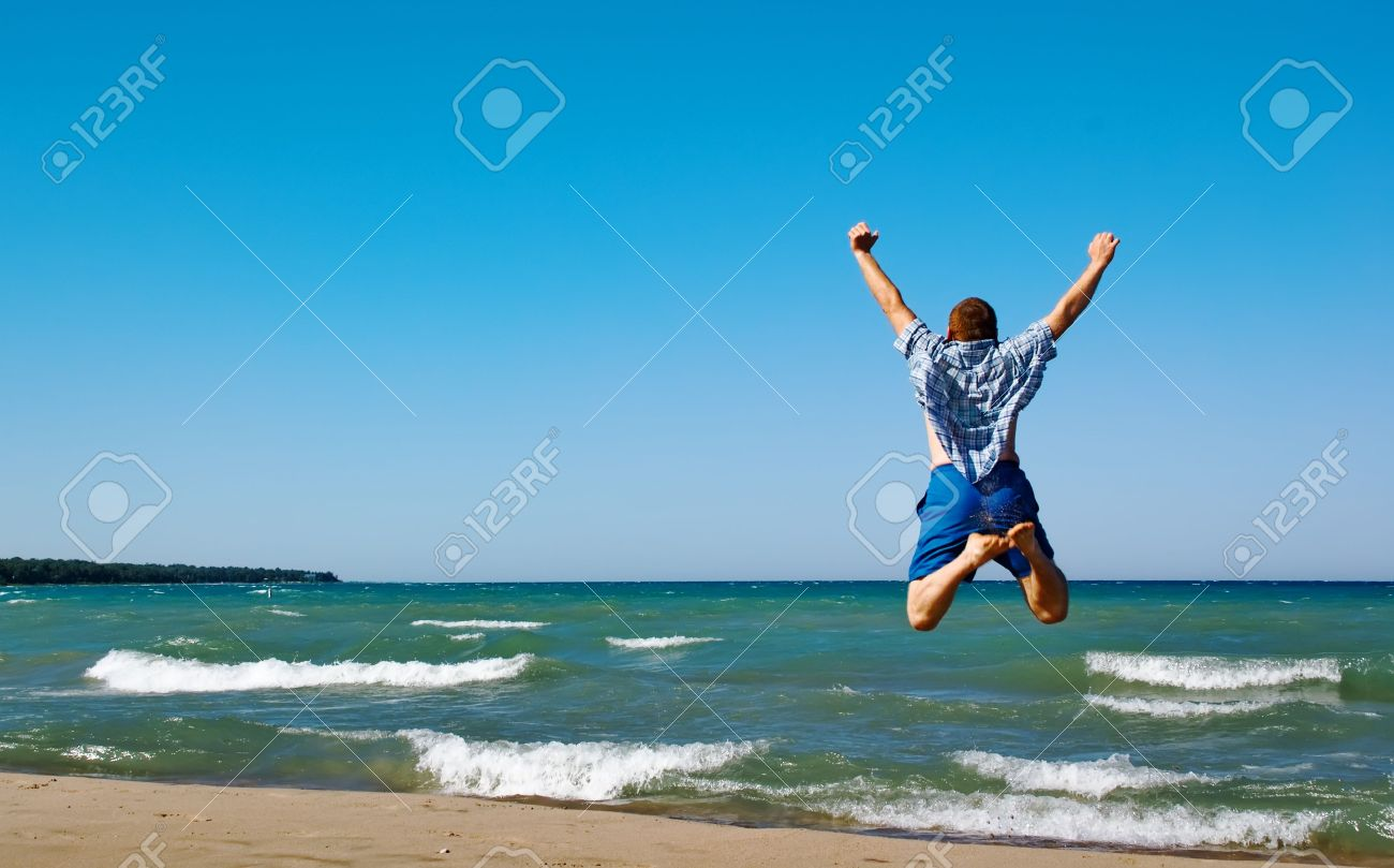 Happy man jumping over sea. Sand beach and blue water. Summer, vacation. - 5420520