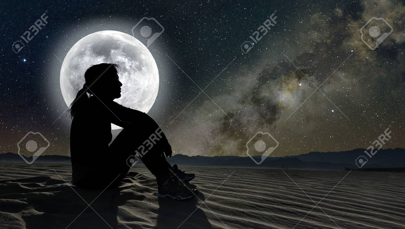 profile of a woman sitting on sand in the moonlight - 71157216