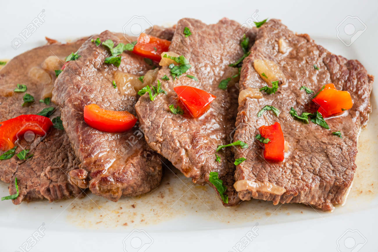 Braised beef cooked with red pepper, served on a plate - 169388207