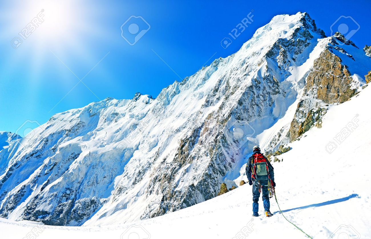Mountaineer sport. A climber reaching the summit of the mountain - 53751086