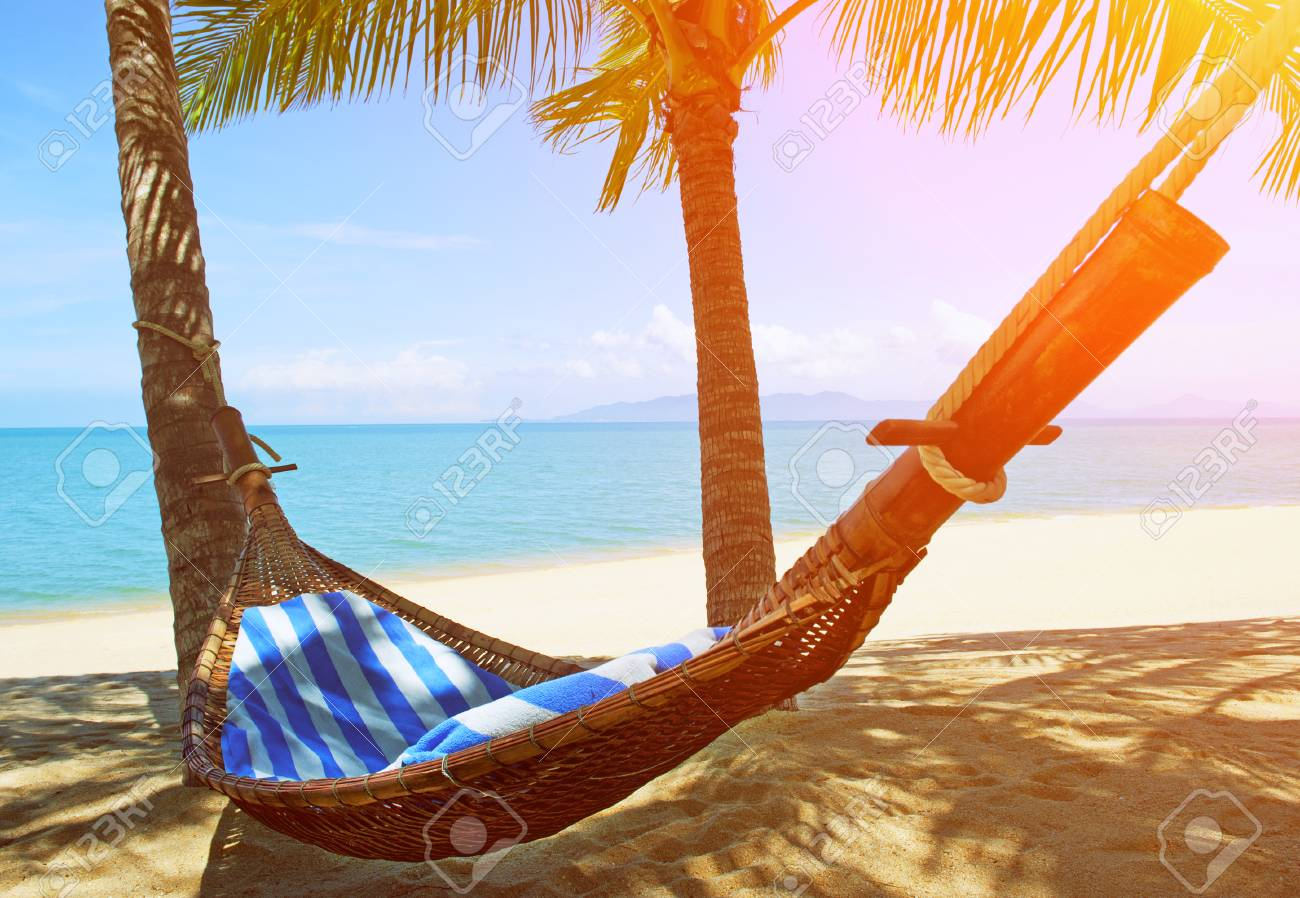 Charming Beautiful Beach. Hammock Between Two Palm Trees On The Beach. Holiday And  Vacation Concept