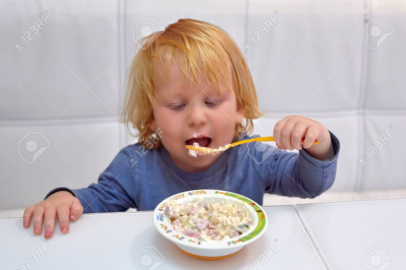 A little boy of three years, a Caucasian with red hair sits at a table and eats with a spoon from a plate, his mouth is dirty with food - 131357713