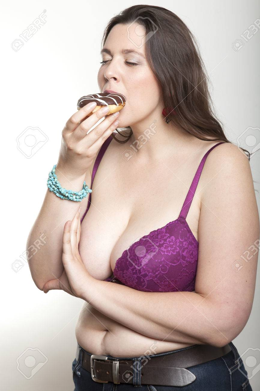 Busty woman in bra and jeans bites into a fresh brown white striped donut  Stock Photo