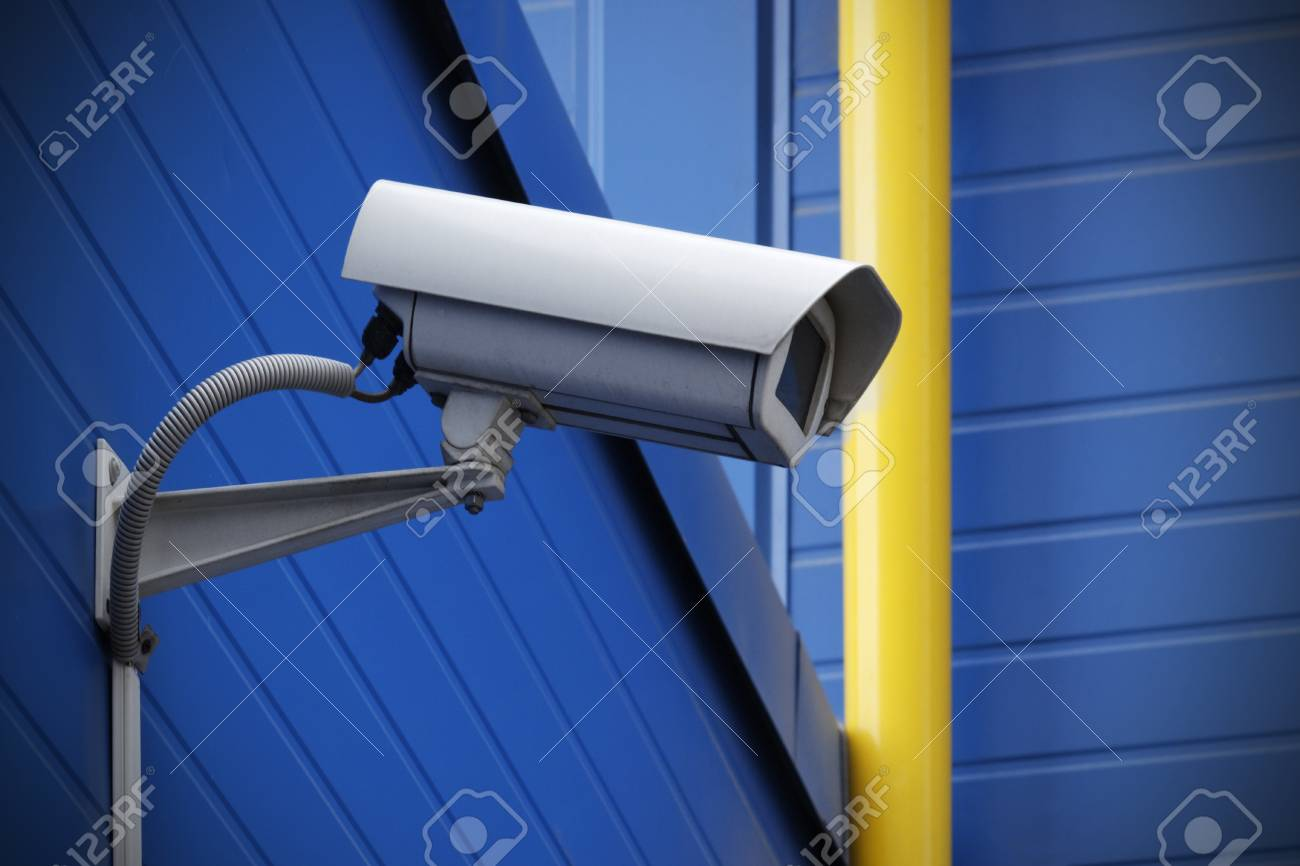 surveillance camera on blue wall next to yellow pipe Stock Photo - 12857861