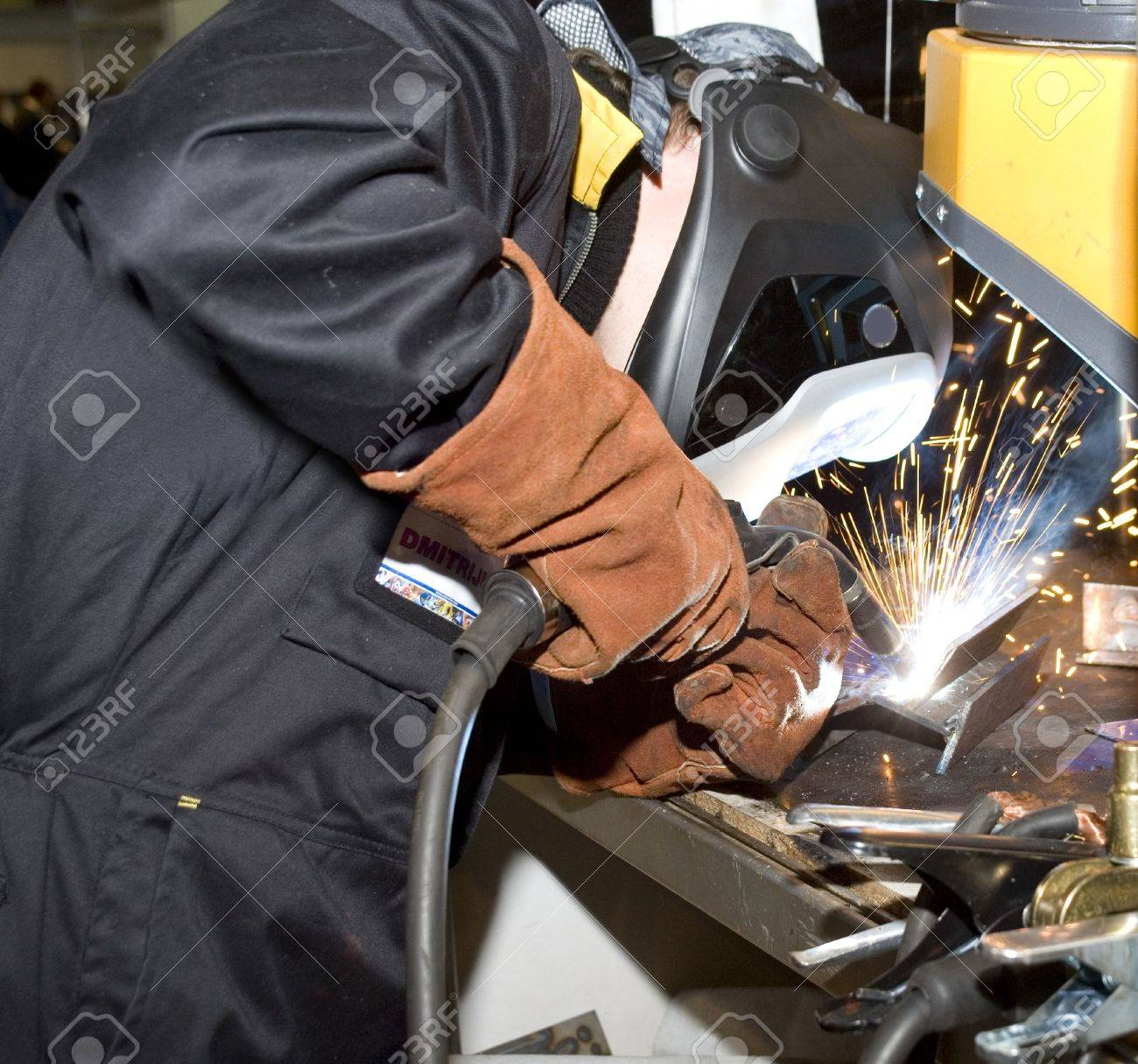 The welder in protective clothes behind job - 6005013