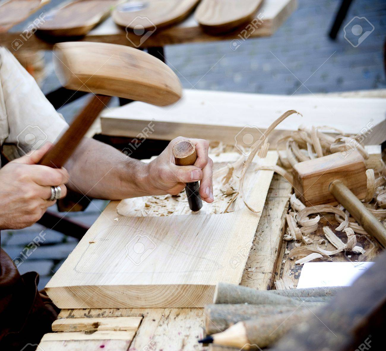 The joiner does a dimple in a board, working with a chisel - 14993523