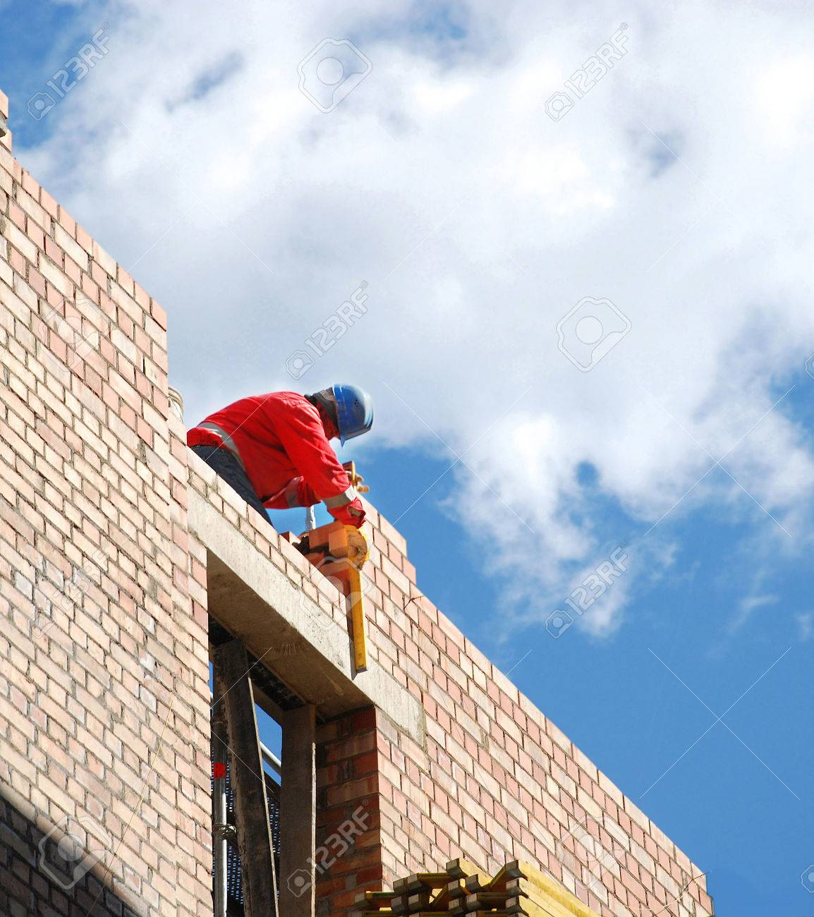 Mason checks the level of quality of masonry brick in the construction of houses - 38324109
