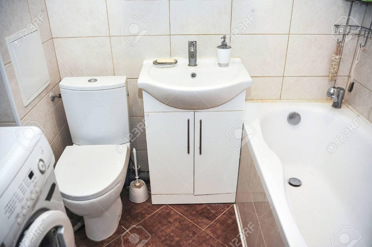 Salle de bain dans un petit appartement avec toilette, lavabo et machine à  laver