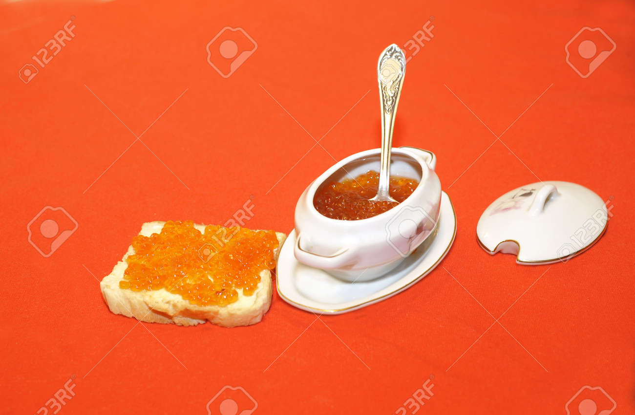 Red caviar in a bowl with a spoon and on a sandwich isolated on red. - 163526093