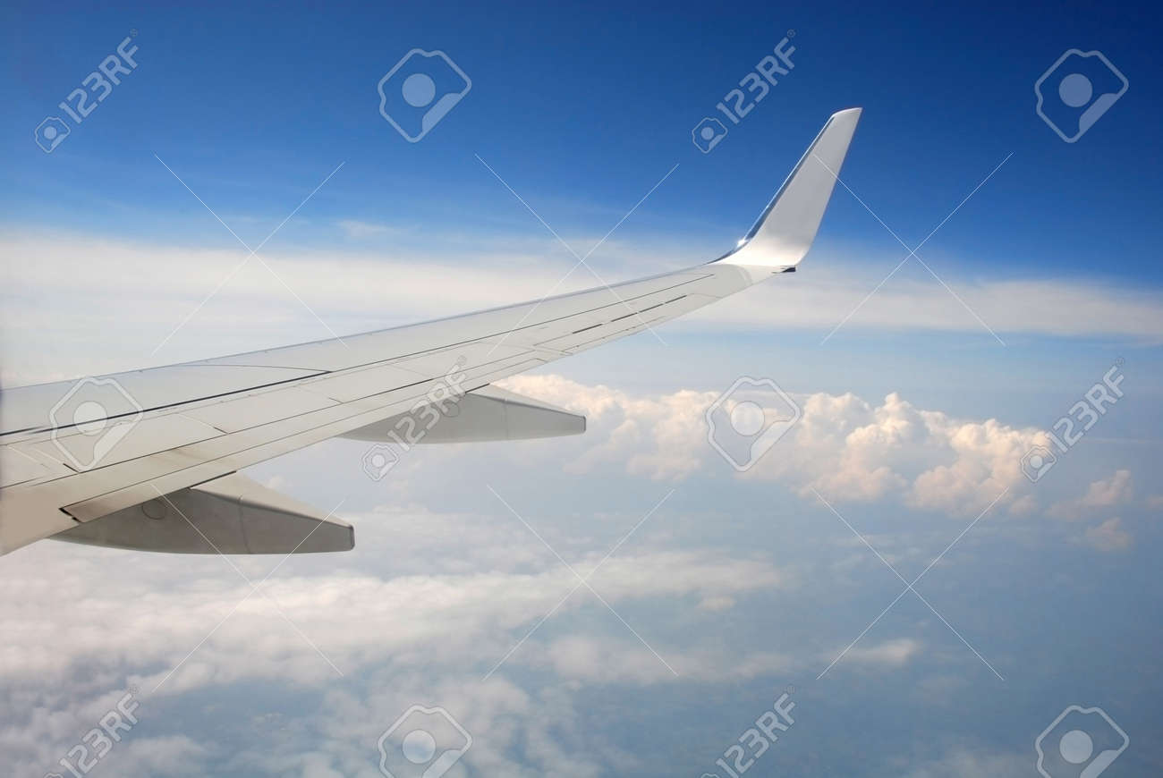 View of the clouds from the cockpit. Cumulus clouds under the wing of a high-flying passenger plane. - 164294444