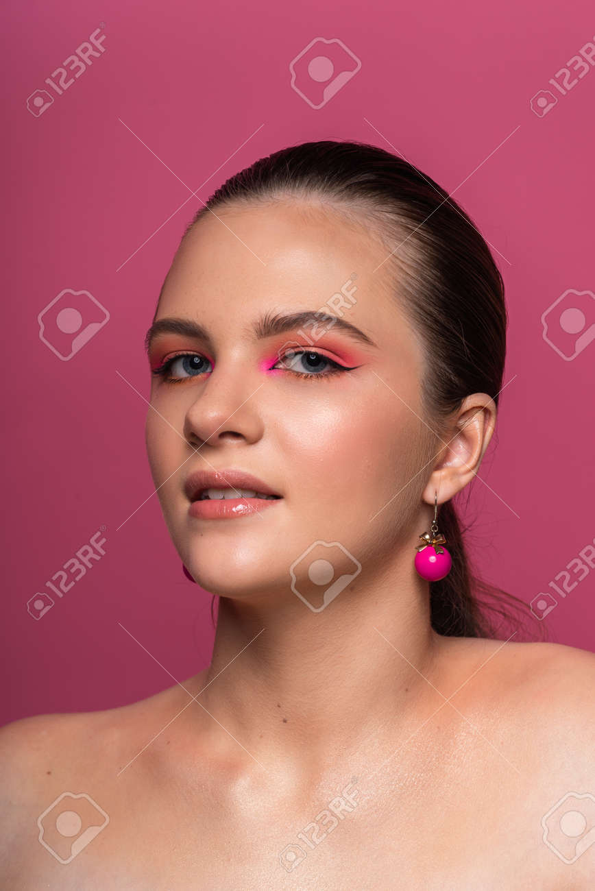 High beauty photo of a lovely young girl with blue eyes, round pink earrings and wonderful professional makeup, with long brown hair. Posing over rosy background. Close-up. Studio shot. Portrait - 167537011