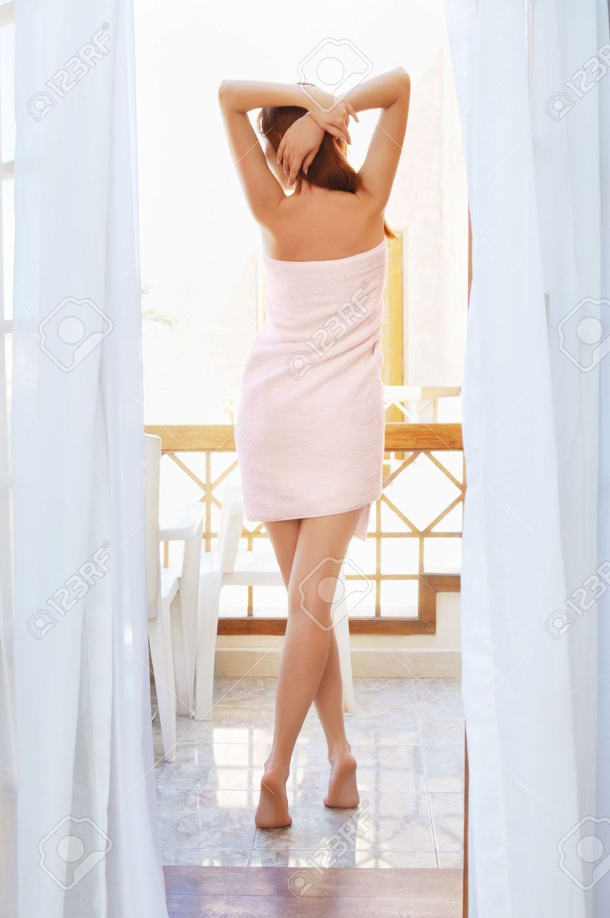 Pretty woman with long legs standing on a balcony after shower Stock Photo - 6133961