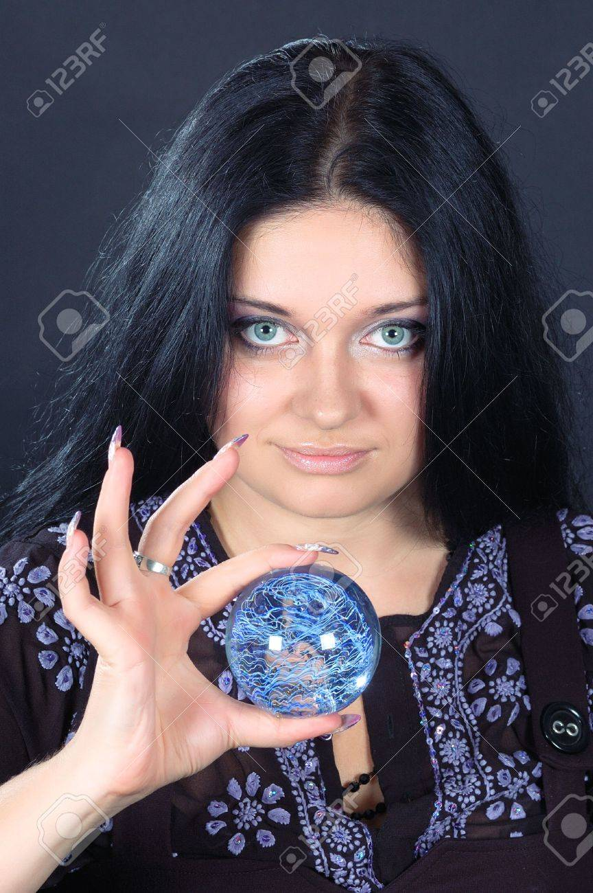 Beautifu smiling black-haired witch holding the magic sphere Stock Photo - 6133985