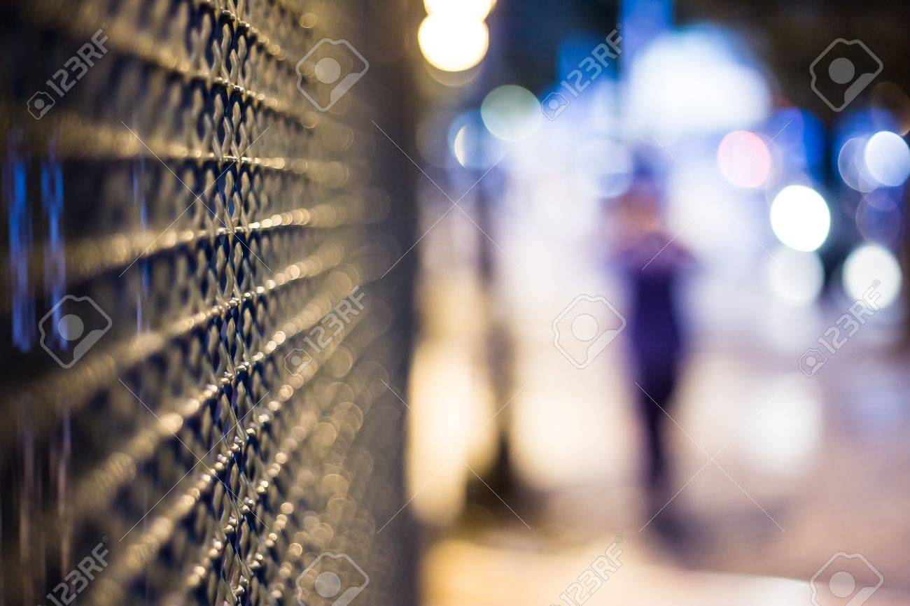 Mysterious night city, blurred figure and fence Stock Photo - 13713819