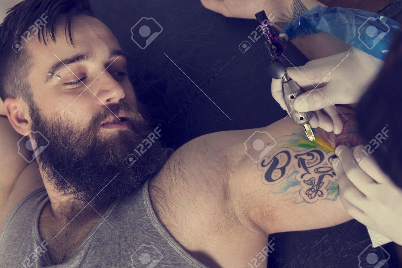 Artiste De Tatouage Homme Tenant Un Pistolet De Tatouage Montrant