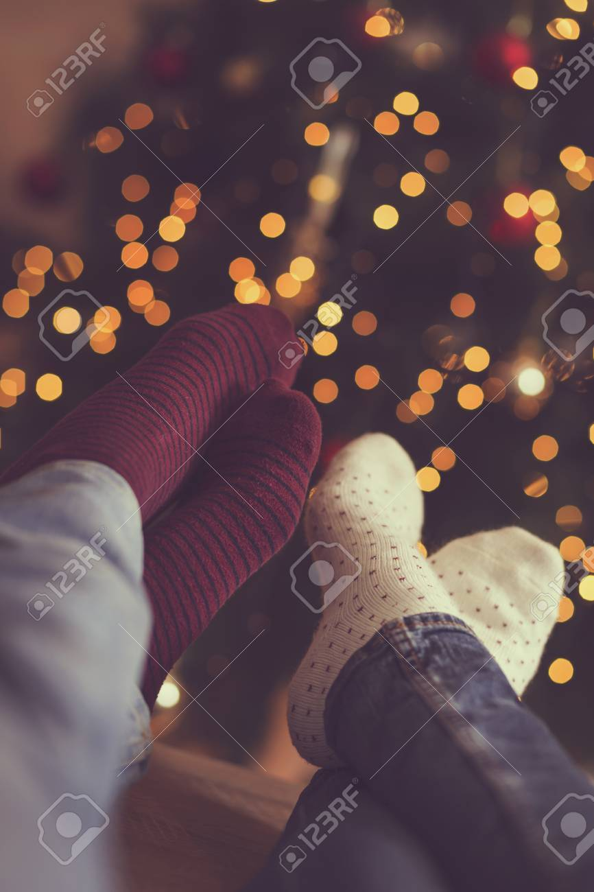 51f82a1ab5c ... Christmas lights in background. Selective focus. Detail of male and  female feet wearing warm winter socks
