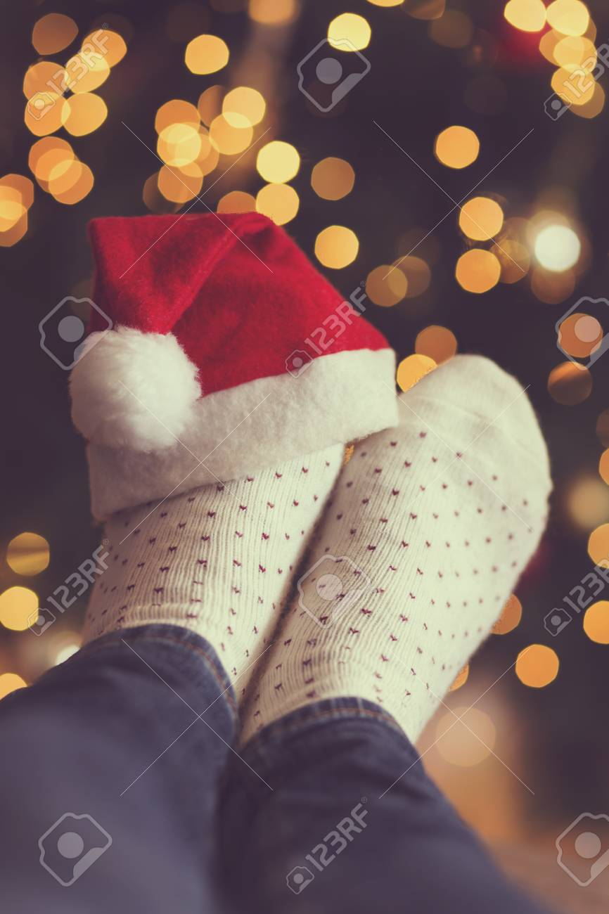 5036ac5bc76 Stock Photo - Woman s feet wearing warm winter socks and small Santa s hat
