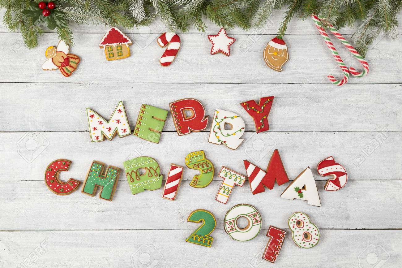 stock photo top view of nicely decorated christmas cookies shaped as letters merry christmas 2018 with pine brunches candy cane and mistletoe on white