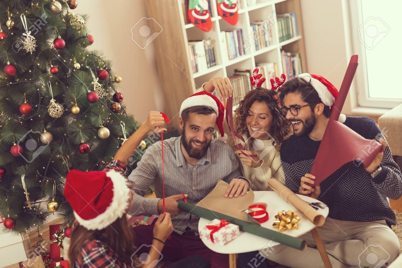 Gruppe Junge Freunde, Die Nahe Bei Dem Weihnachtsbaum Sitzen ...
