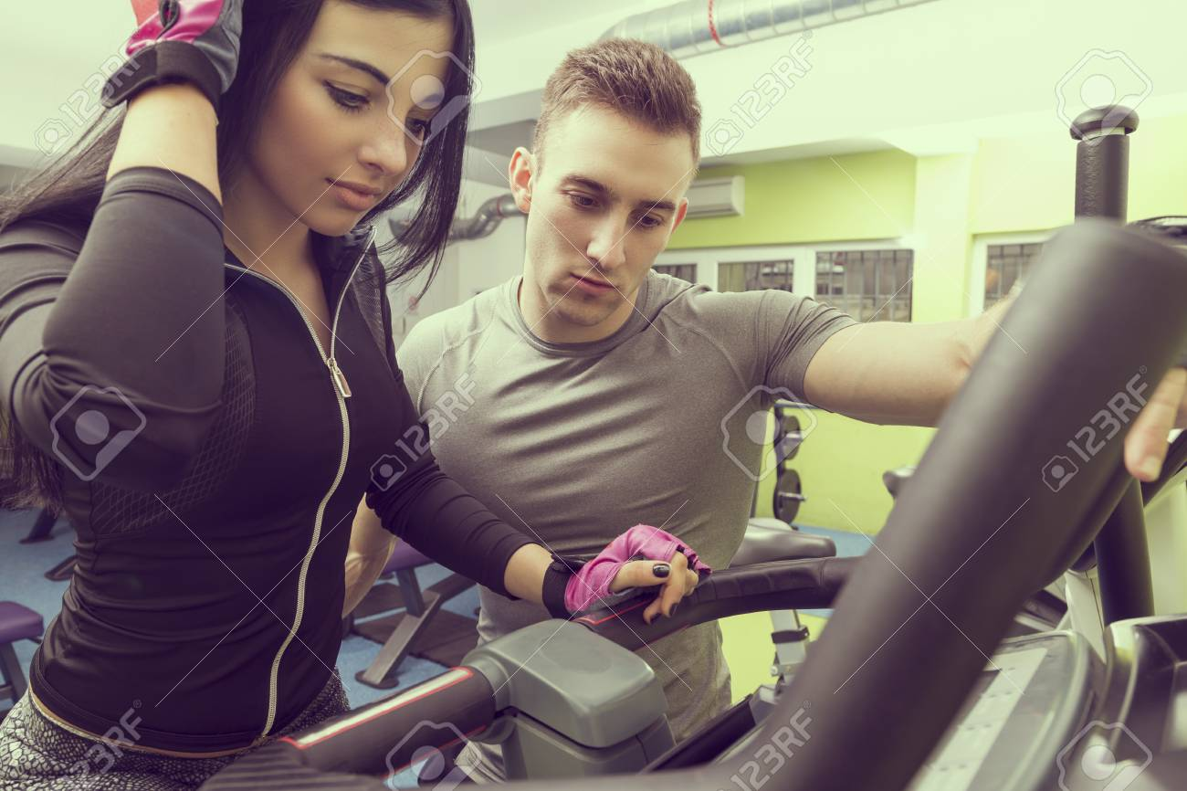 Personal trainer giving a workout instructions to a female gym