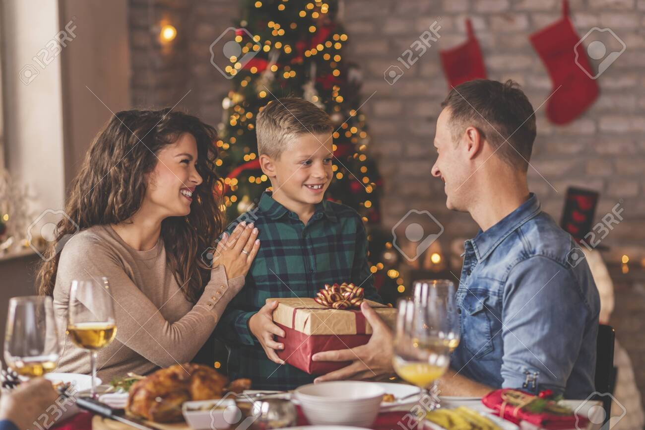 Family having Christmas dinner at home, gathered around the table, enjoying their time together; mother and father giving Christmas present to their son - 158283320