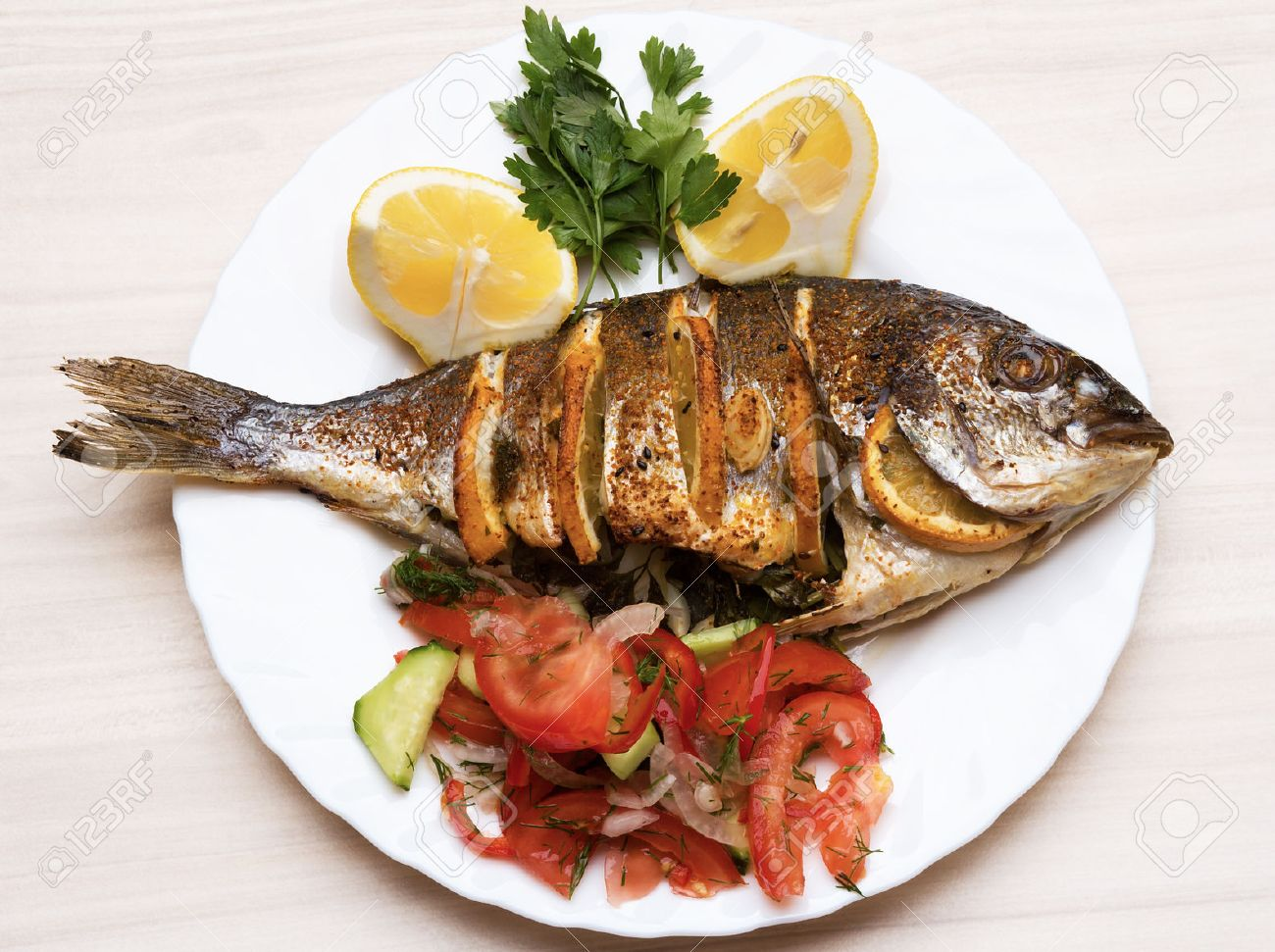cooked fish sea bream fish with lemon parsley garlic stock photo