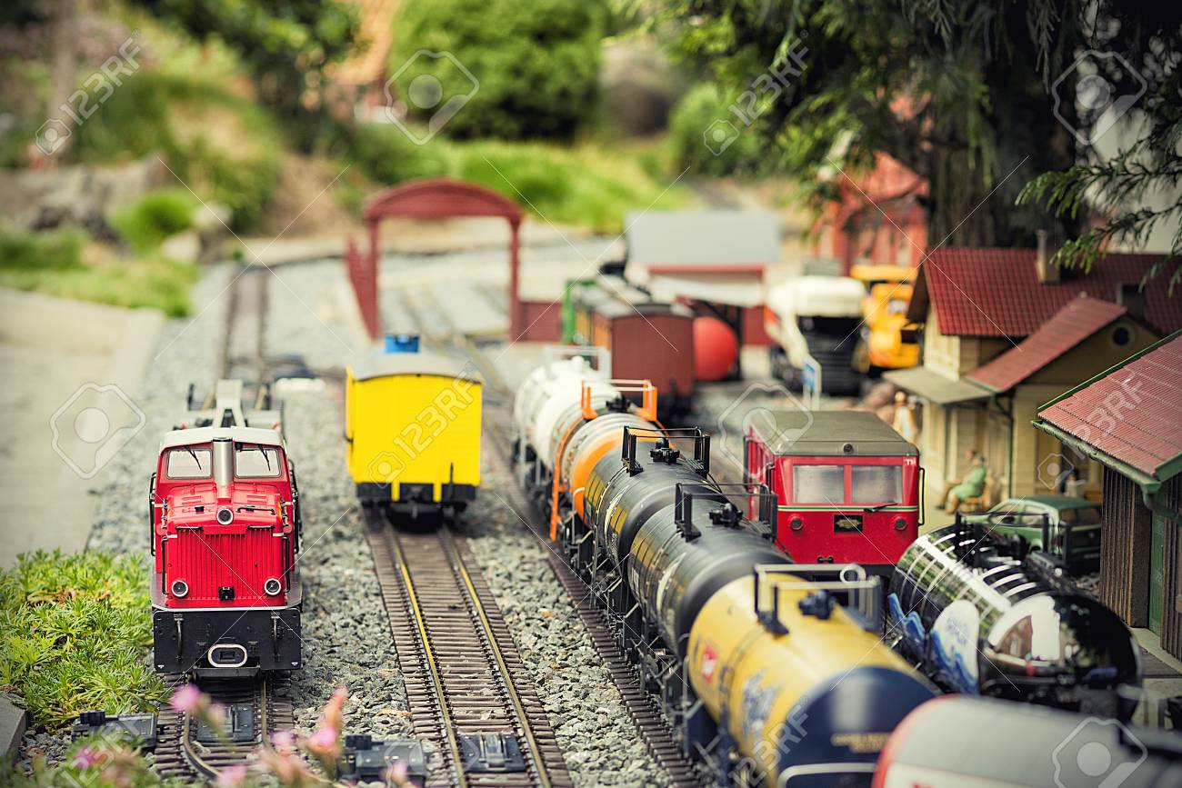 Set of red electric model railway locomotive and layout with