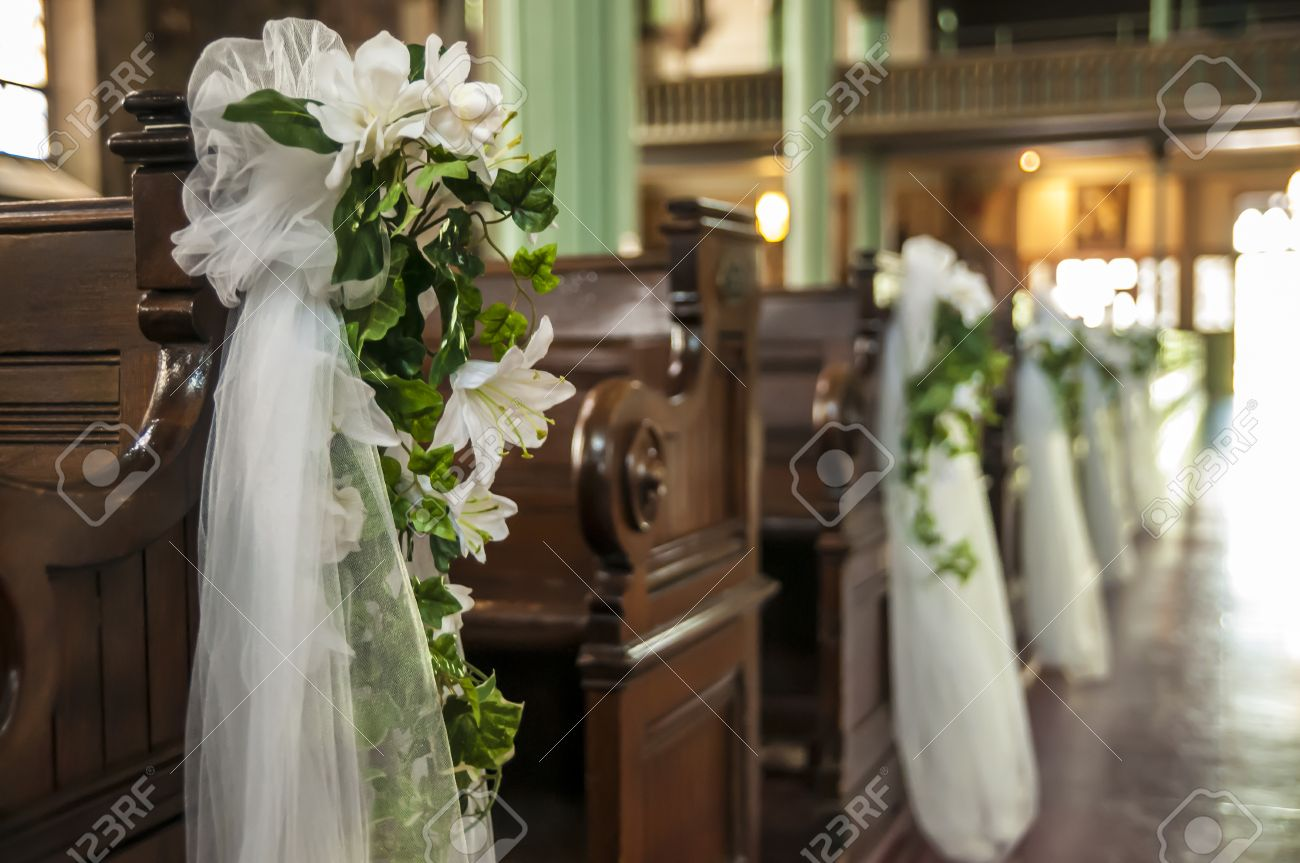 Wedding decoration white flowers and green leafs hanging on the stock photo wedding decoration white flowers and green leafs hanging on the church benches junglespirit Choice Image
