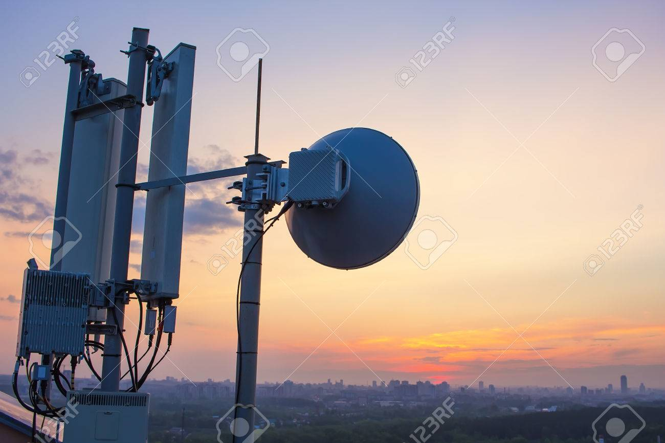 base station with a radio relay antenna on the background of a sunset over the city - 57562876