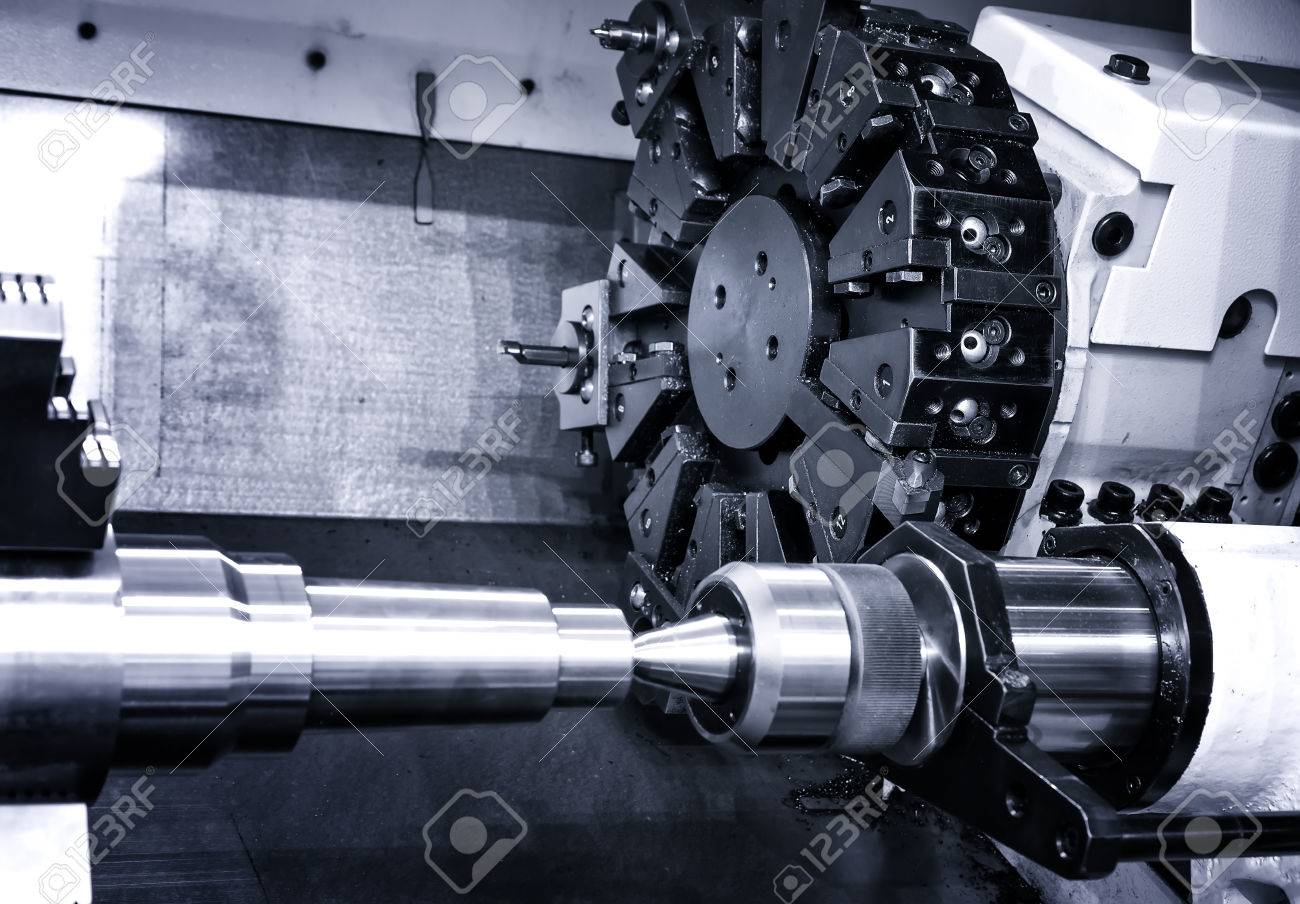Rotating head with drilling machine bits and tools in high precision mechanics plant at CNC lathe in workshop - 64067881