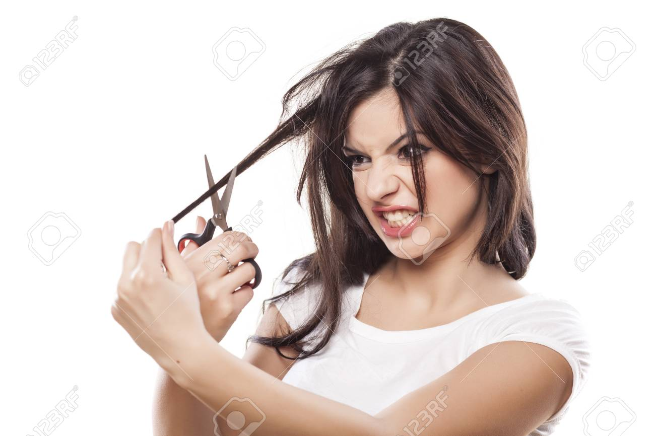 Angry girl cutting her hair with scissors stock photo 69135467