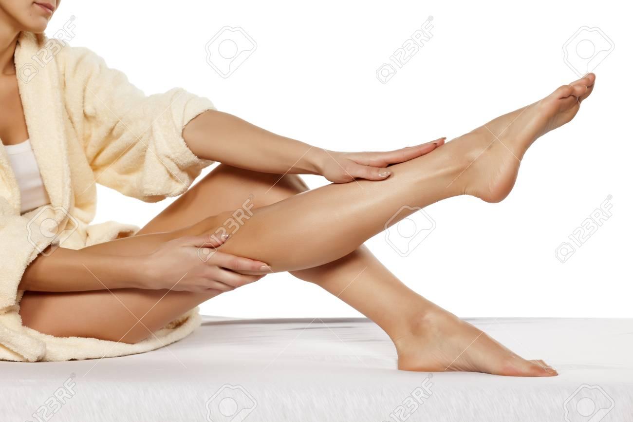 Jolie femme a appliqué une crème sur ses jambes banque d images et